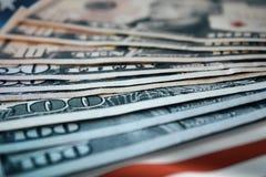 Stapel US-Dollars mit US-Flaggen-Hintergrund stockbilder
