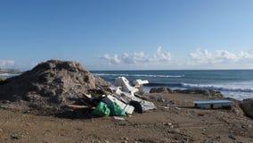 Stapel van afval en plastiek op het strand met sterke golven die de rotsachtige kust raken Overzees en oceaanverontreiniging stock videobeelden