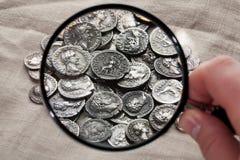 Stapel van antieke die muntstukken door een vergrootglas worden gezien Stock Foto