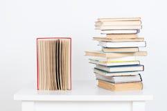 Stapel van boek met harde kaftboeken en oud open boek op witte muurachtergrond Zoek naar relevante en noodzakelijke informatie Royalty-vrije Stock Afbeelding
