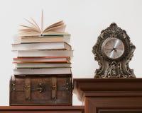 Stapel van boeken die zich op een oude boomstam, naast antiek bevinden cloc Stock Foto