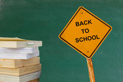 Stapel van boeken en verkeersteken met woord TERUG NAAR SCHOOL met bordachtergrond Royalty-vrije Stock Foto's