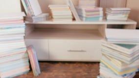 Stapel van boeken op de vloer en op de kast blur stock videobeelden