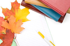 Stapel van boeken, schrijven-boek, pen en de herfstbladeren Stock Foto