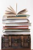 Stapel van boekenkosten op een oude borst Stock Afbeelding