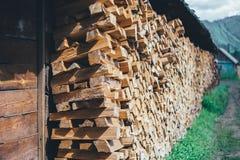 Stapel van brandhout dichtbij de omheining in het platteland stock fotografie