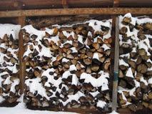 Stapel van brandhout door sneeuw wordt behandeld die Stock Foto's