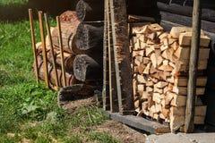 Stapel van brandhout naast oude houten plattelandshuisjemuur, zon aangestoken gras royalty-vrije stock foto
