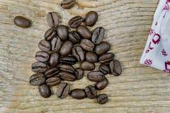 Stapel van de bonen van de braadstukkoffie op een houten lijst Stock Foto