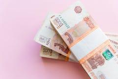 Stapel van 5000 die roebelspakken op roze worden ge?soleerd Het concept rijkdom, winsten, zaken en financi?n Stapelgeld in royalty-vrije stock afbeeldingen