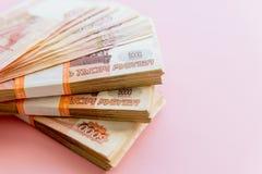 Stapel van 5000 die roebelspakken op roze worden ge?soleerd Het concept rijkdom, winsten, zaken en financi?n Stapelgeld in royalty-vrije stock foto's