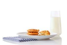 Stapel van drie eigengemaakte pindakaaskoekjes en de helften koekjes op witte ceramische plaat op blauw servet en glas melk Stock Fotografie