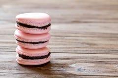 Stapel van drie Franse cakes van woestijn roze die macaron op houten achtergrond worden geïsoleerd royalty-vrije stock afbeeldingen