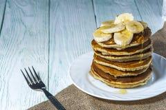 Stapel van eigengemaakte pannekoeken met banaanplakken en honing op witte plaat met vork en linnenservet op houten achtergrond Stock Fotografie