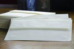 Stapel van enveloppen en boekenachtergrond met benadrukte diepte van gebied Stock Afbeelding