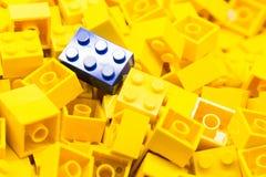 Stapel van gele kleurenbouwstenen met selectief nadruk en hoogtepunt op één bijzonder blauw blok die beschikbaar licht gebruiken Stock Foto