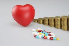 Stapel van geneeskunde en rood hart met gouden muntstukken Stock Foto's