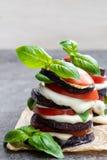 Stapel van geroosterde aubergine met tomaat en mozarella op grijze steenlijst stock foto