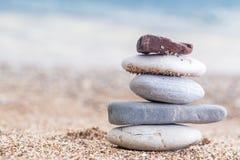 Stapel van gestapelde stenen op het zandige strand bij Adriatische overzees Stock Foto's