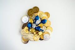 Stapel van gouden en zilveren Chanoekamuntstukken met uiterst kleine die dreidels op wit wordt geïsoleerd stock foto's