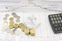 Stapel van gouden en zilveren muntstuk naast giftdoos en calculator Royalty-vrije Stock Afbeeldingen