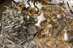 Stapel van gouden gebruikte muntstukken en uitstekend vaatwerk, kroonluchter en kleine standbeelden voor verkoop bij een markt stock foto