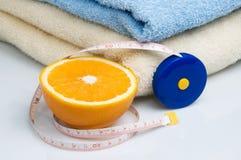 Stapel van handdoeken, meetlint en sinaasappel Stock Fotografie