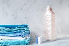 Stapel van handdoeken met omhoog detergens op wasserij achtergrondspot stock fotografie