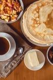 Stapel van heerlijke eigengemaakte pannekoeken of blini met chocolade, kop thee, boter Stock Afbeeldingen