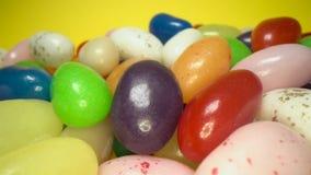 Stapel van heerlijke kleurrijke het kauwen suikergoedachtergrond Kleurrijke snoepjes op gele achtergrond stock videobeelden