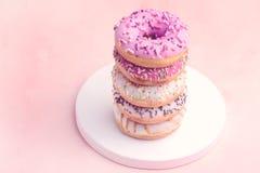 Stapel van Heerlijke Mooie Donuts op Roze Achtergrond Houten Tray Pink Lilac en Witte Donuts-Gestemde Exemplaar Ruimte Verticale  royalty-vrije stock foto