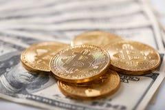 Stapel van het gouden gecodeerde bitcoins liggen op dollarbankbiljetten die nieuwe futuristische digitale munt voorstellen Stock Afbeelding