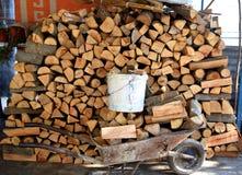 Stapel van het houten logboeken en hoogtepunt van de wielkruiwagen van hout royalty-vrije stock afbeeldingen