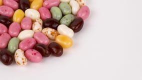Stapel van het kleine boon gevormde suikergoed van de suikergelei Het roteren op de draailijst stock videobeelden