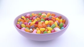 Stapel van het kleine boon gevormde suikergoed van de suikergelei Het roteren in purpere kom op de draailijst Geïsoleerde stock video