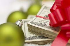 Stapel van Honderd Dollarsrekeningen met Boog dichtbij Kerstmisornamenten Royalty-vrije Stock Afbeelding