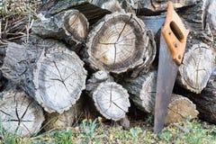 Stapel van houten timmerhout en oude handsaw royalty-vrije stock afbeeldingen