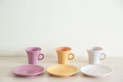 Stapel van kleurrijke moderne koppen van koffie op houten lijst Stock Afbeeldingen