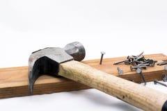 Stapel van klinknagels, spijkers en een hamer op houten stuk op witte achtergrond stock foto