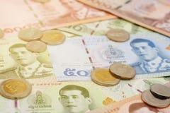 Stapel van nieuwe Thaise Bahtbankbiljetten en muntstukken stock foto's