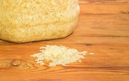 Stapel van ongekookte rijst tegen van plastic container met rijst Royalty-vrije Stock Fotografie