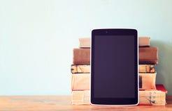 Stapel van oude boeken en tablet over houten plank Nieuwe technologieconcept Zaal voor tekst Stock Foto's