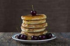 Stapel van pannekoeken met bessen en honing die over druipen Stock Foto
