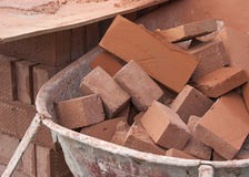 Stapel van rode bakstenen in een kruiwagen Stock Fotografie