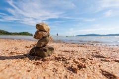 Stapel van rots tegen toneel van het strand van het de zomerzand en bewolkte blu Royalty-vrije Stock Fotografie
