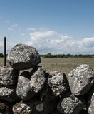 Stapel van rotsen die bovenop elkaar als omheining op een gebied worden gestapeld stock foto's