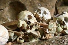 Stapel van schedels door de ingang aan TampangAllo-begrafenishol in Tana Toraja indonesië stock afbeelding