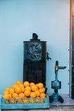 Stapel van sinaasappelen en oude sapmachine stock fotografie