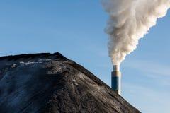 Stapel van steenkool met de schoorsteen van een steenkoolelektrische centrale in backg Royalty-vrije Stock Afbeeldingen