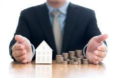 Stapel van stijgend muntstukken en huismodel met zakenman stock afbeelding